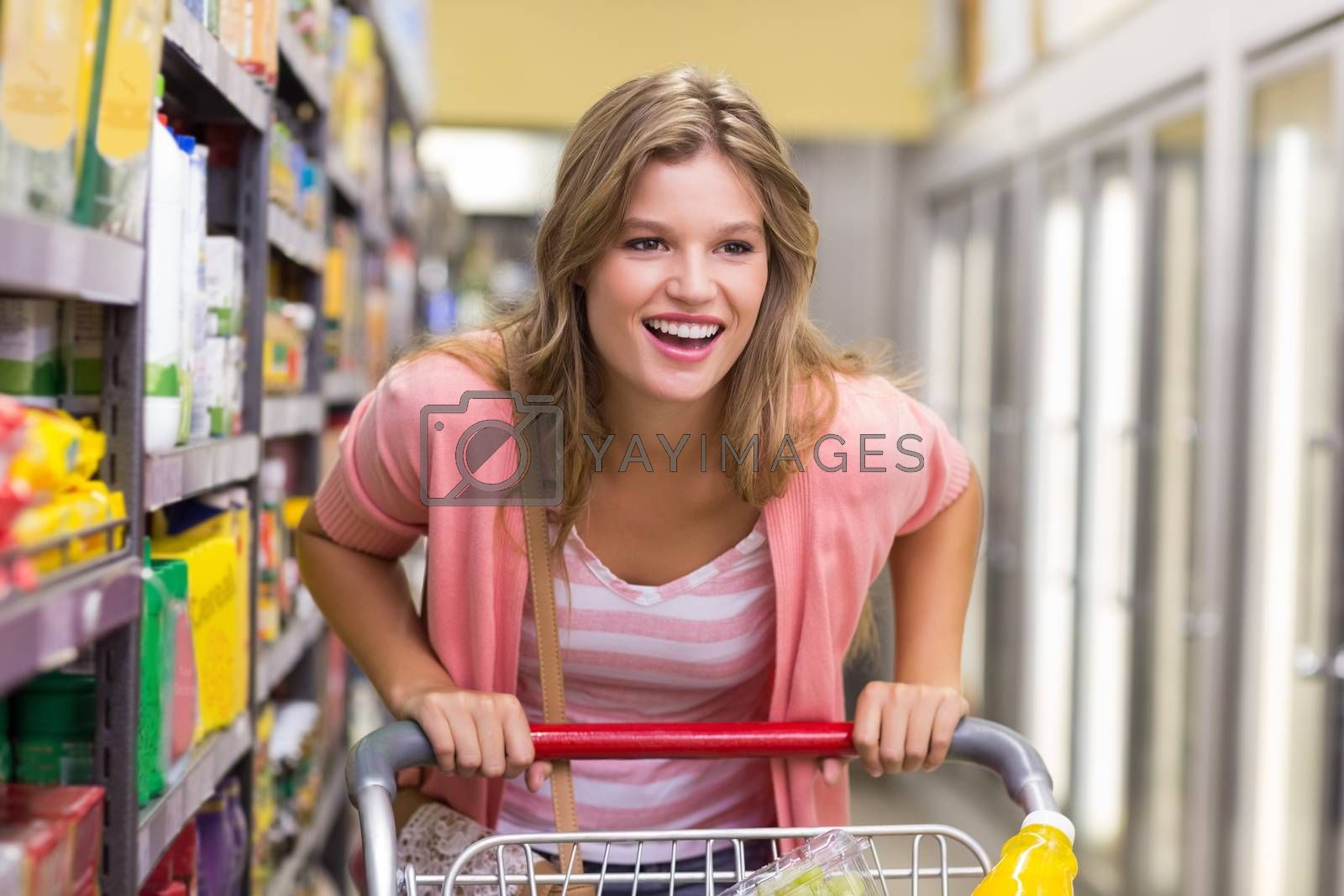 Royalty free image of Smiling pretty blonde woman buying a products  by Wavebreakmedia