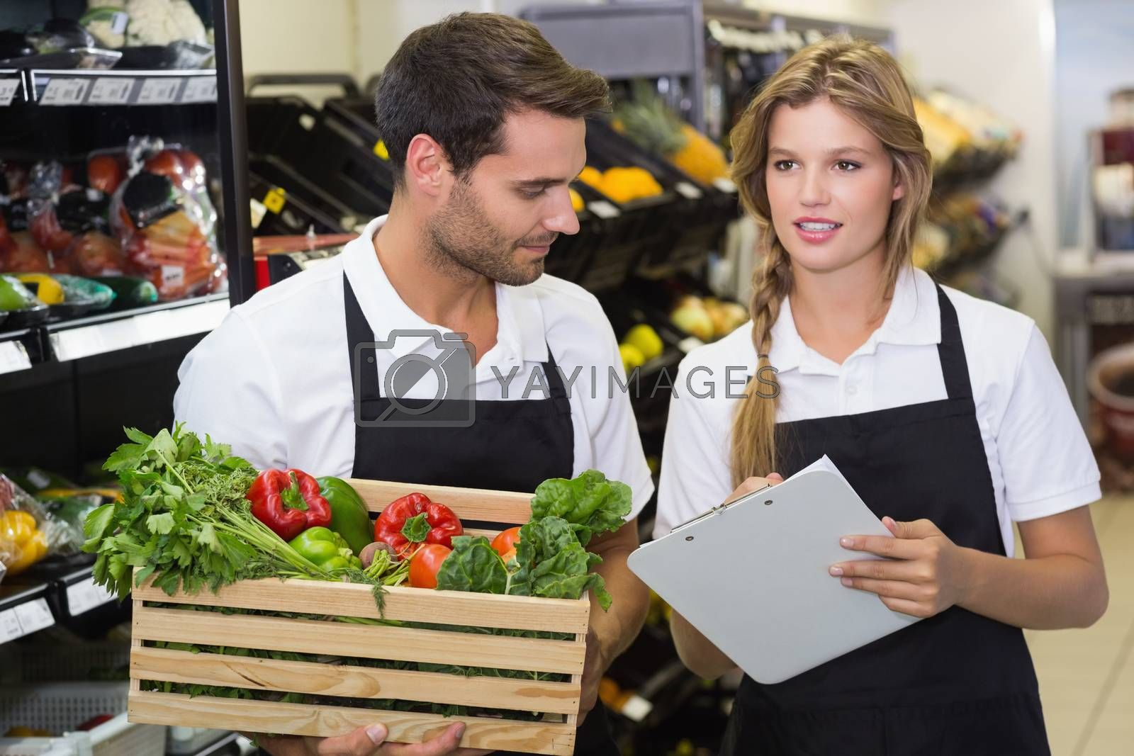 Royalty free image of Two colleagues holding a box with fresh vegetables and writing on notepad by Wavebreakmedia