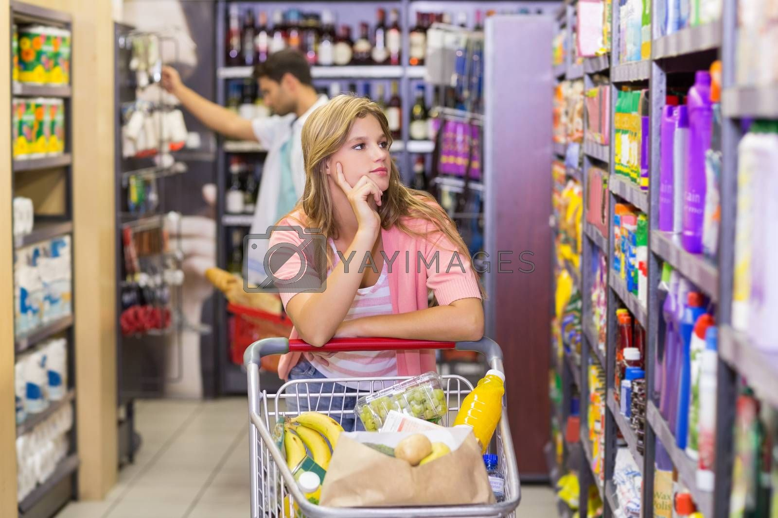 Royalty free image of Pretty young woman looking at shelf  by Wavebreakmedia
