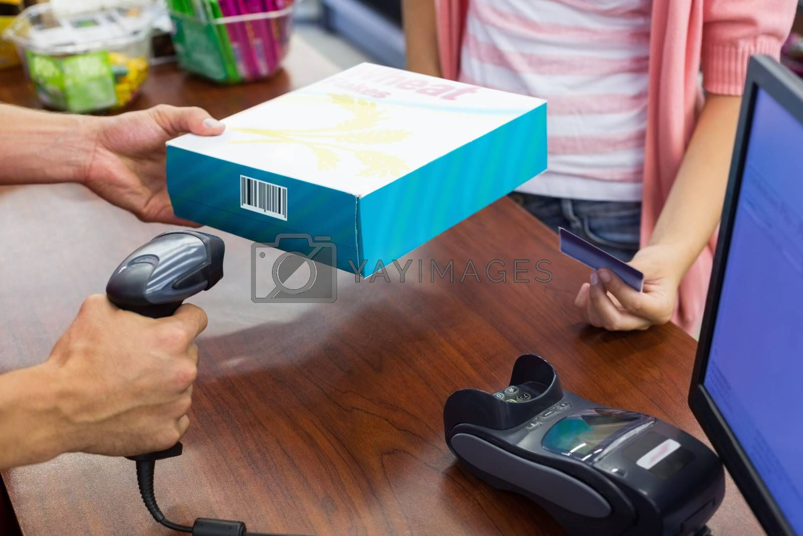Royalty free image of Smiling woman at cash register paying with credit card and scan a product  by Wavebreakmedia