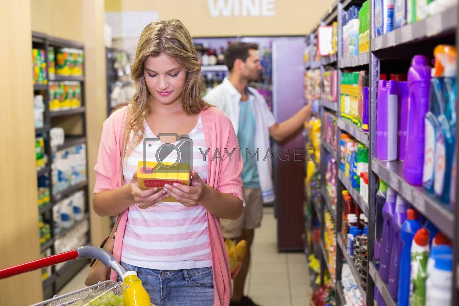 Royalty free image of Smiling pretty young woman buying a products  by Wavebreakmedia
