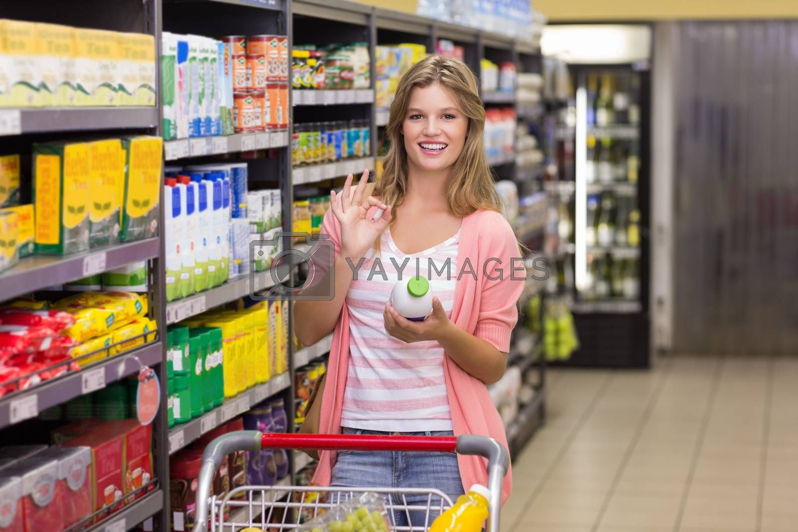 Royalty free image of Portrait of a smiling pretty blonde woman buying products  by Wavebreakmedia