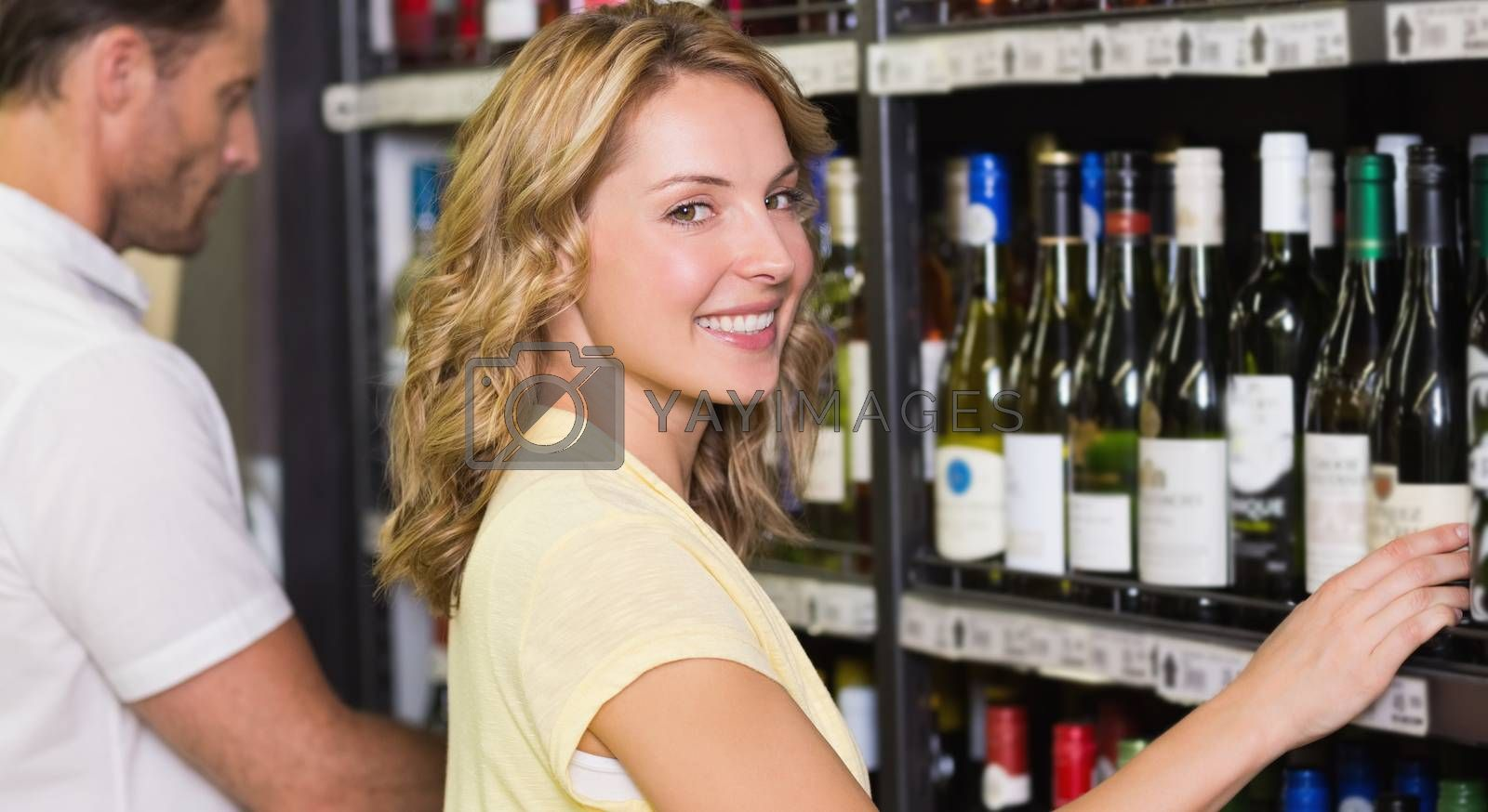 Royalty free image of Portrait of smiling pretty woman buying a wine bottle  by Wavebreakmedia