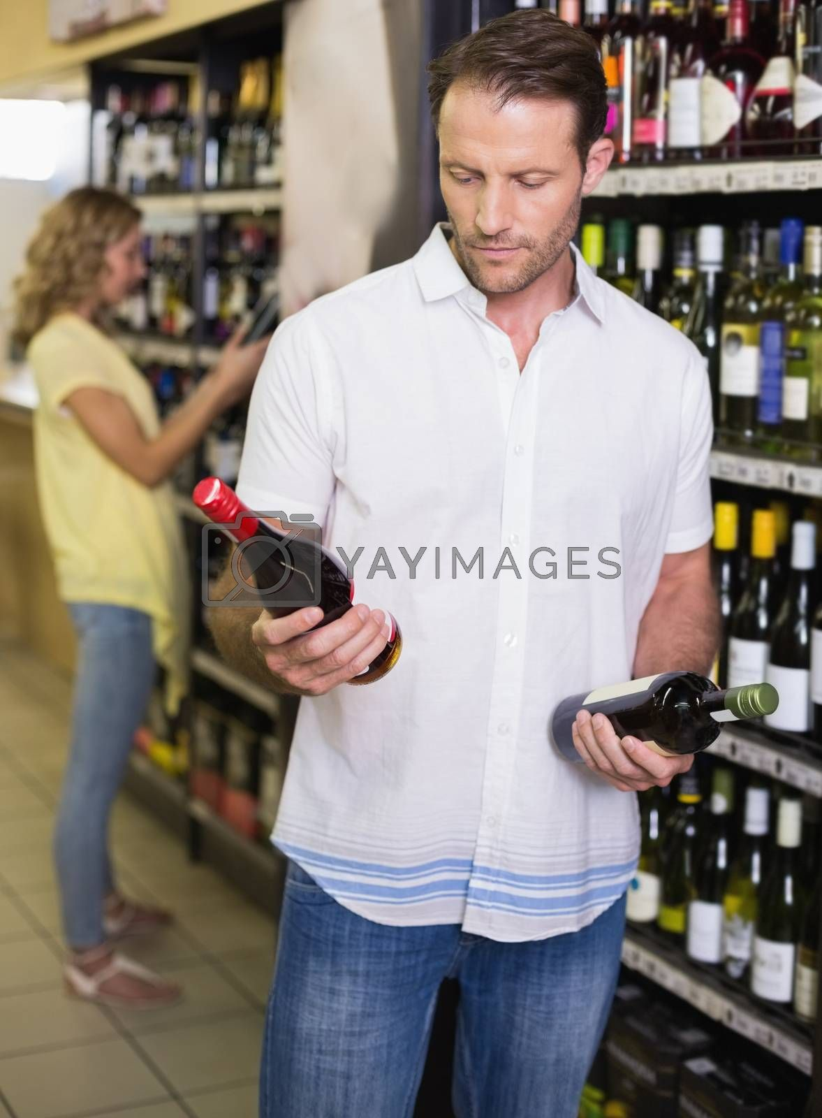 Royalty free image of A handsome showing a wine bottle  by Wavebreakmedia