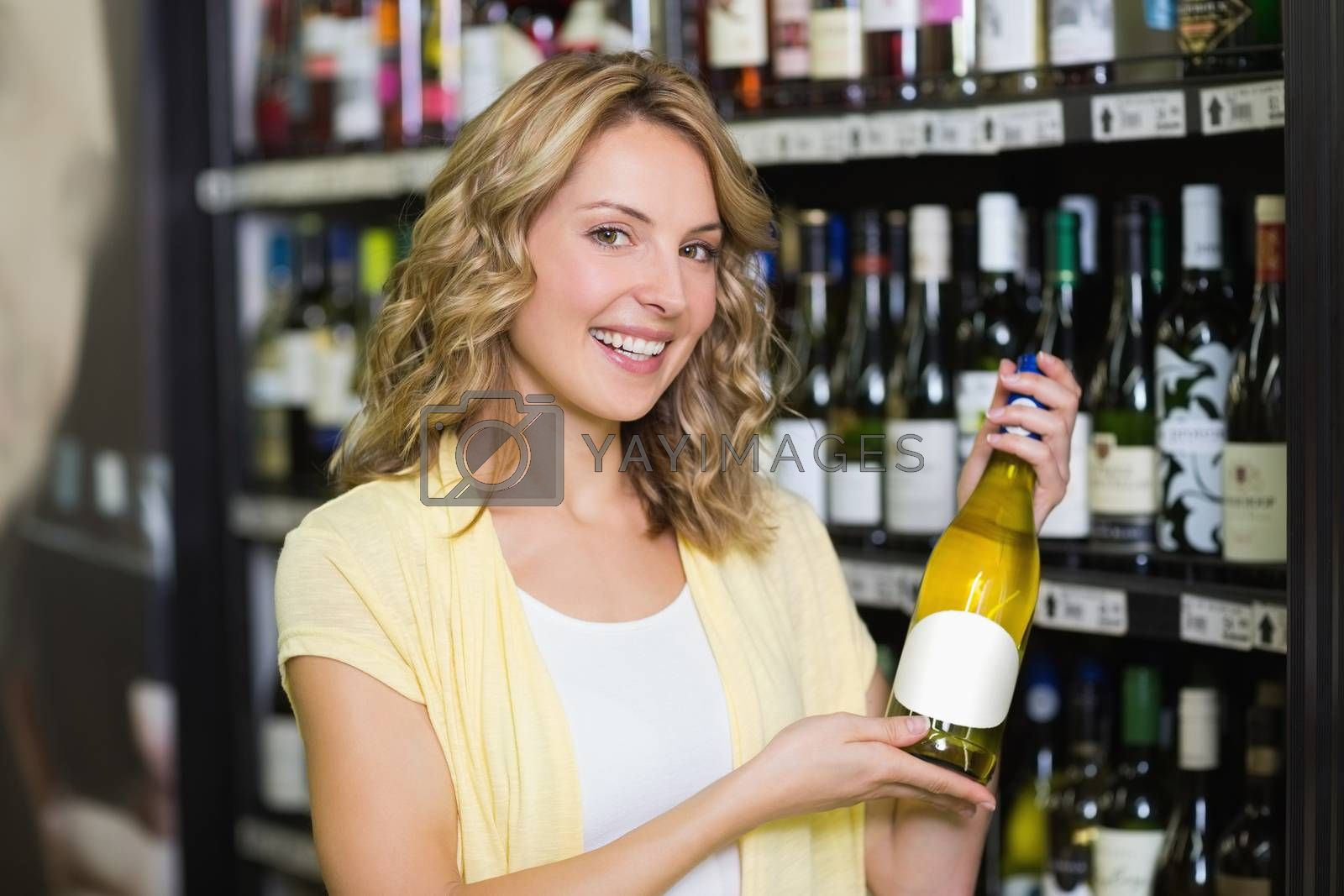 Royalty free image of Portrait of a smiling pretty blonde woman showing a wine bottle  by Wavebreakmedia