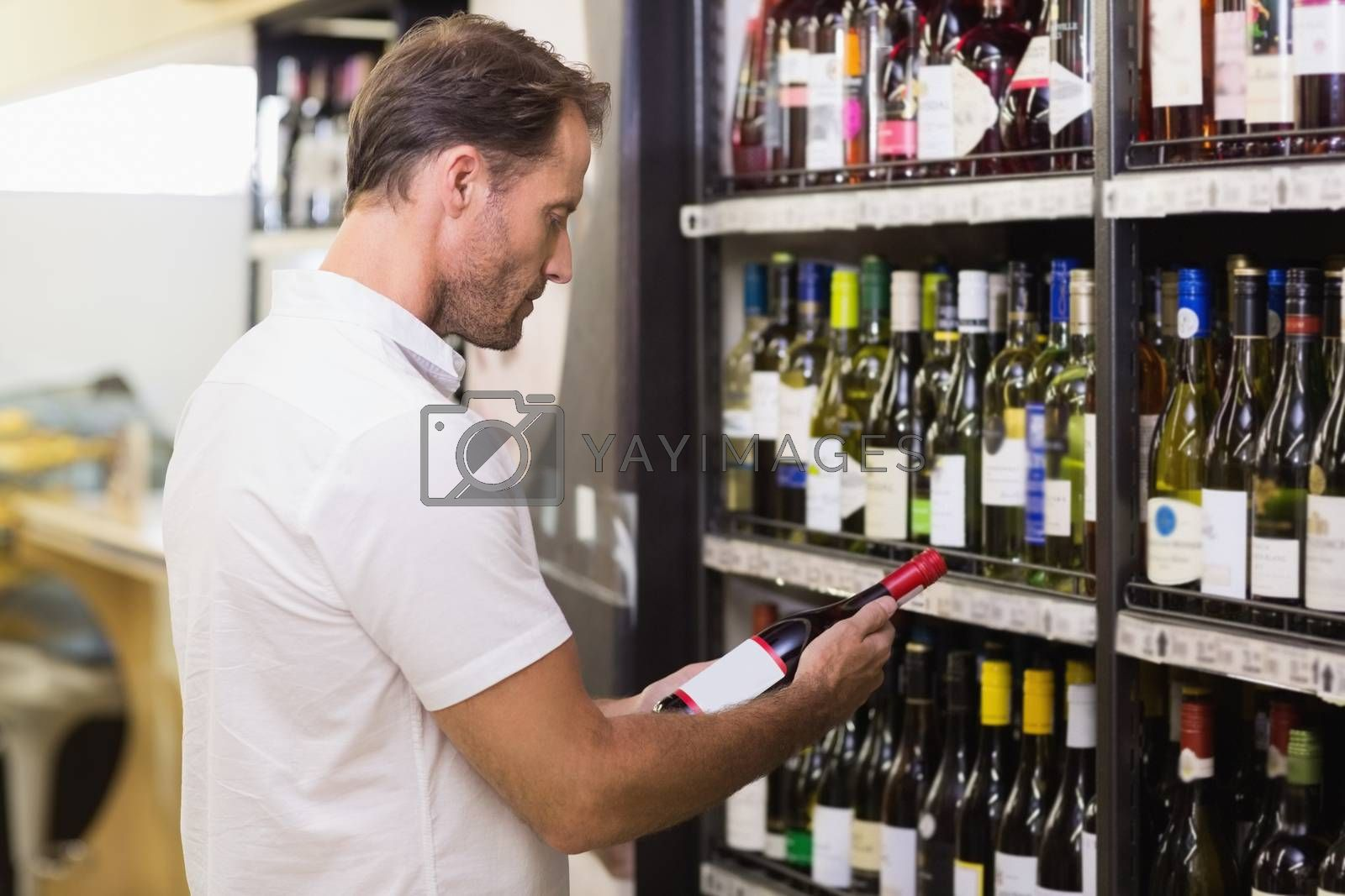 Royalty free image of Handsome looking at wine bottle  by Wavebreakmedia