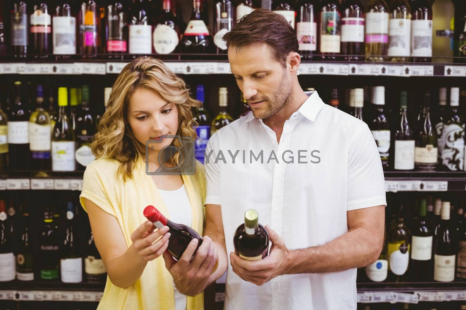 Royalty free image of Casual couple looking at wine bottle  by Wavebreakmedia
