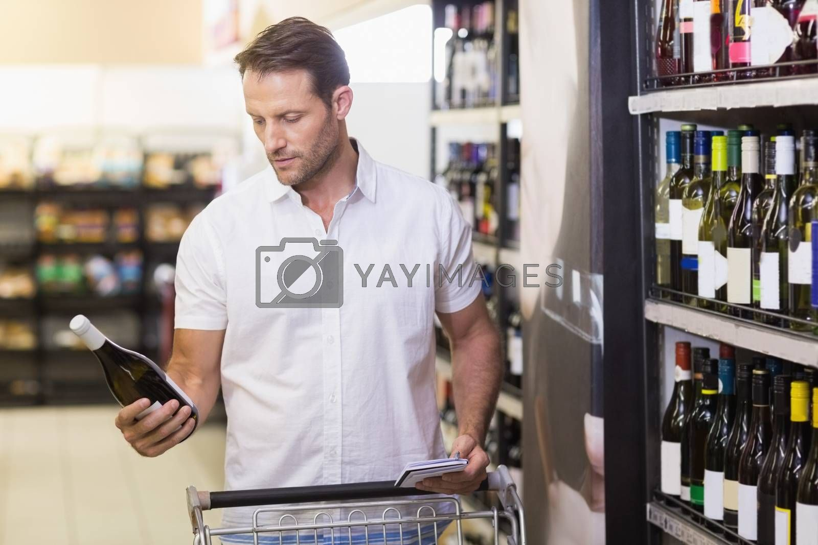 Royalty free image of Handsome looking at a wine bottle having in her hands  by Wavebreakmedia
