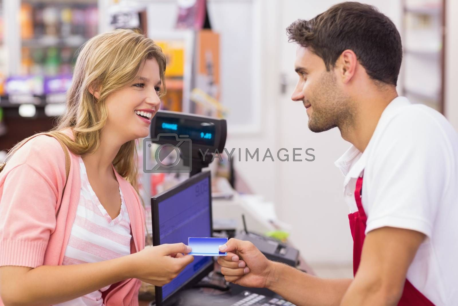 Royalty free image of Smiling woman at cash register paying with credit card by Wavebreakmedia