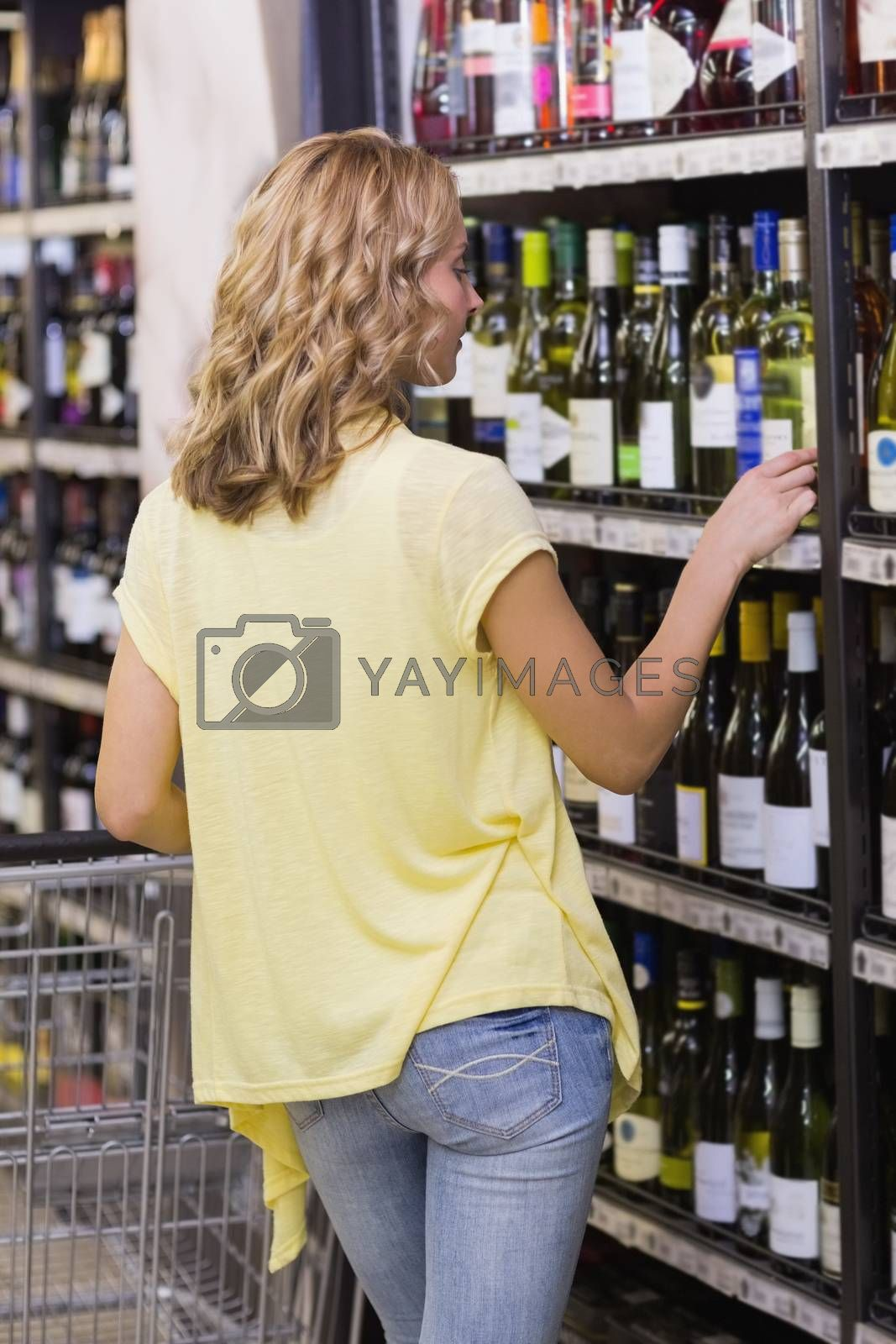 Royalty free image of Back view of a blonde woman looking at a wine bottle  by Wavebreakmedia