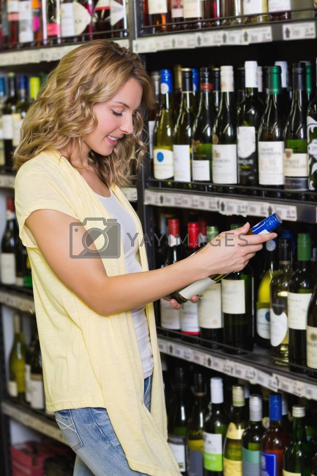 Royalty free image of Smiling pretty blonde woman looking at wine bottle  by Wavebreakmedia