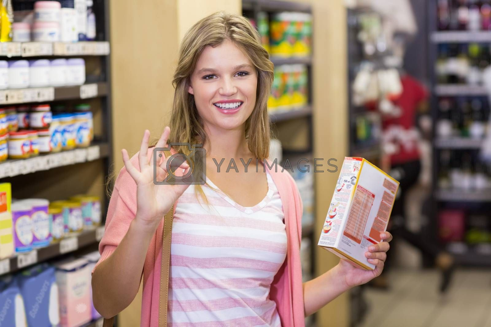 Royalty free image of Portrait of a smiling young pretty woman doing a sign of the hand  by Wavebreakmedia