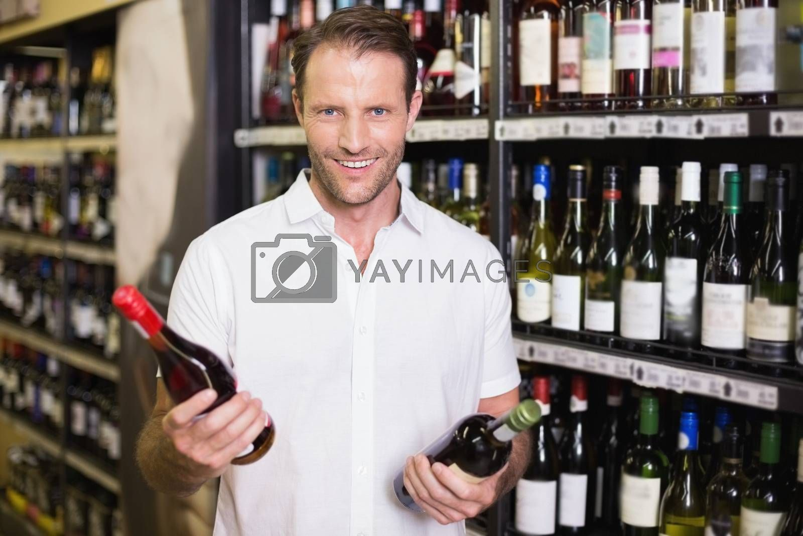 Royalty free image of Portrait of a smiling handsome showing a wine bottle  by Wavebreakmedia