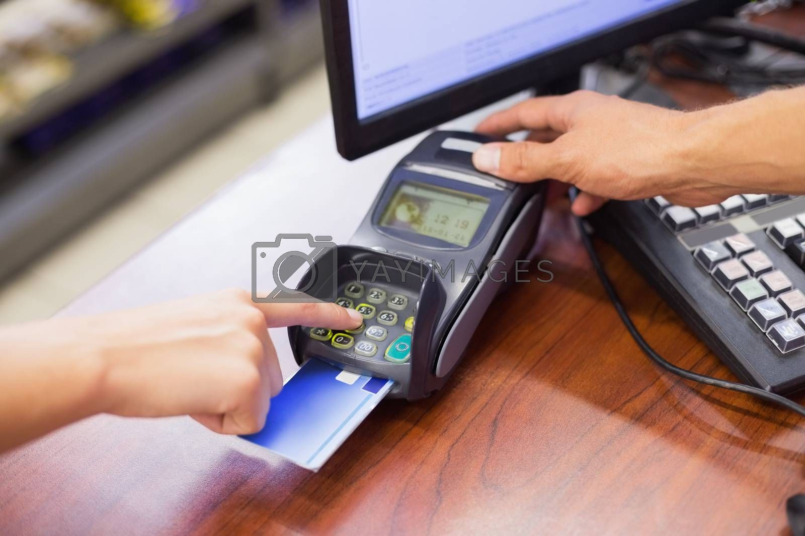 Royalty free image of Woman paying with her credit card and doing his pin code  by Wavebreakmedia