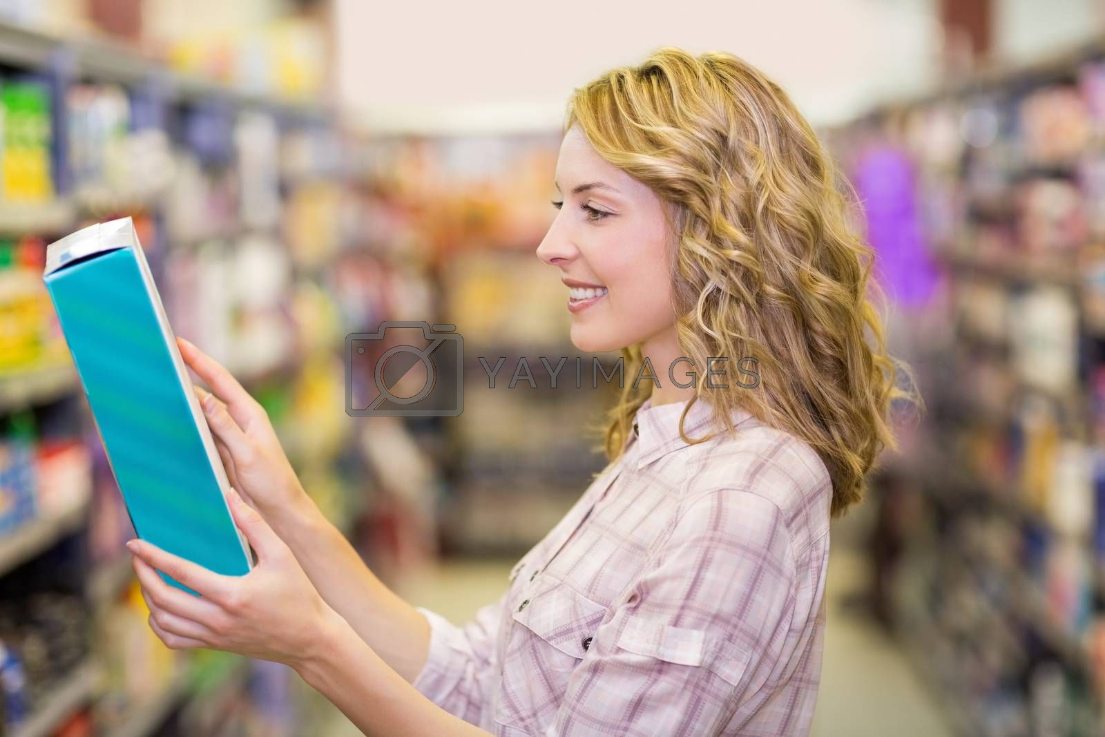 Royalty free image of Side view of smiling pretty blonde woman reading a book  by Wavebreakmedia