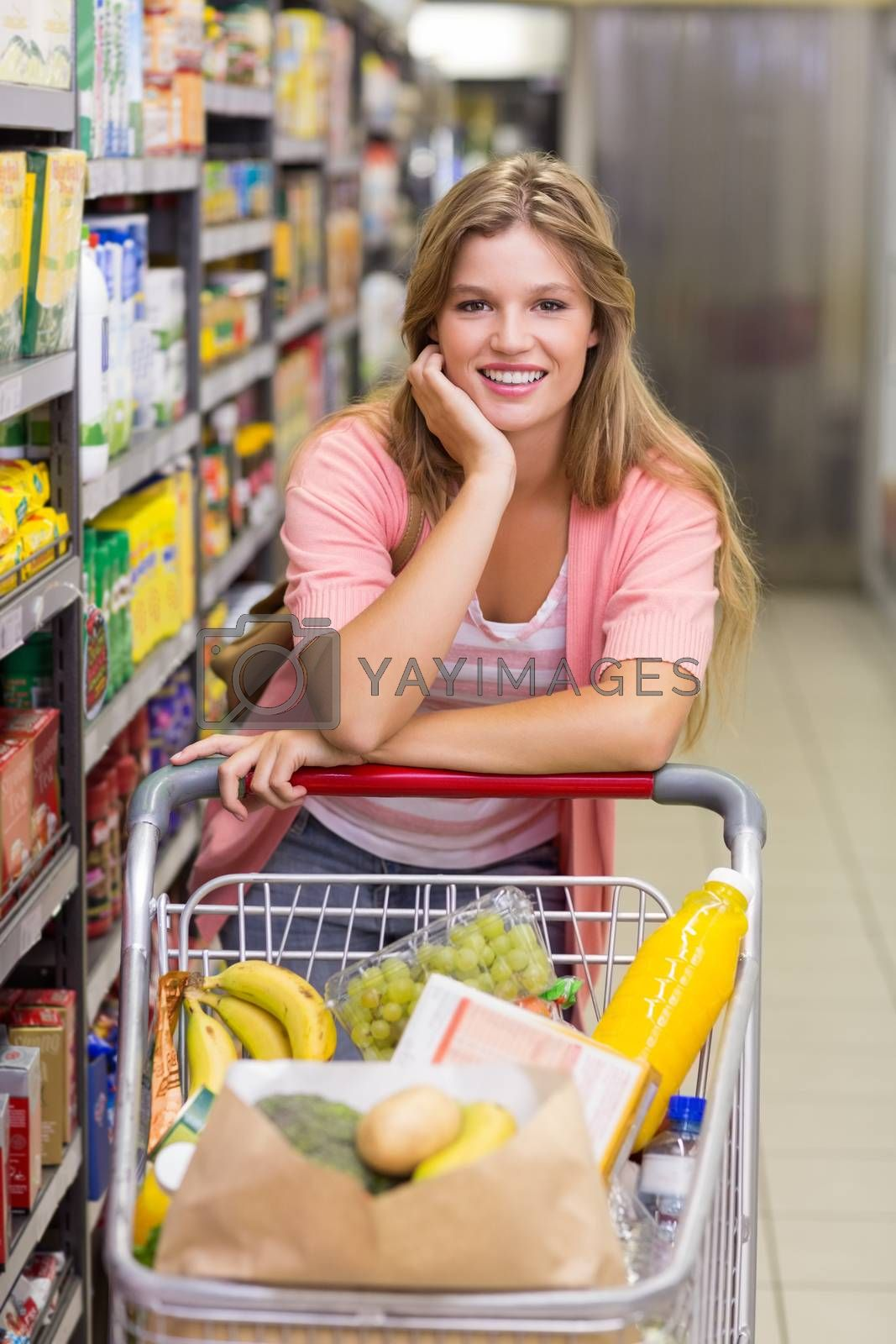 Royalty free image of Portrait of a smiling pretty blonde woman in aisle  by Wavebreakmedia