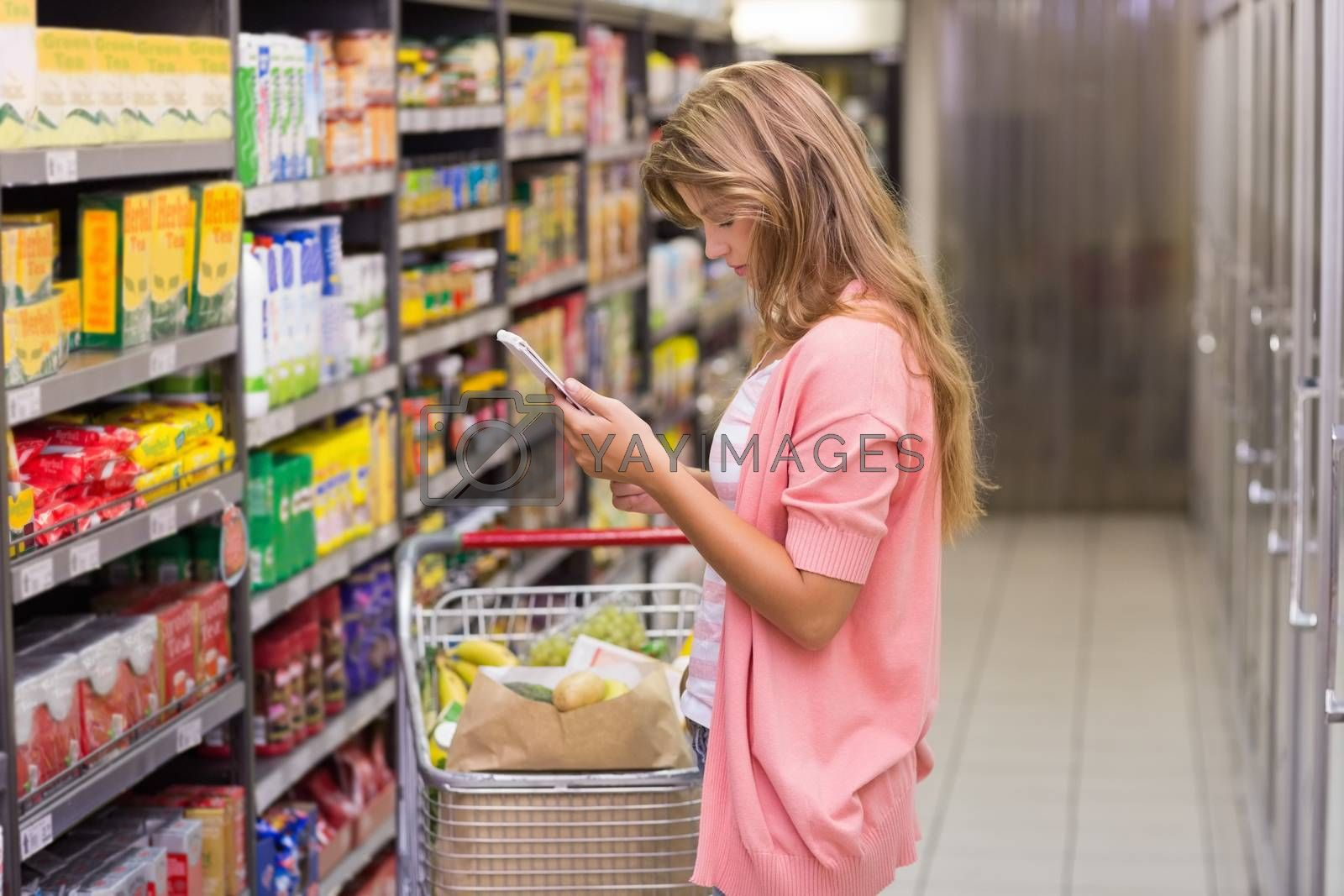 Royalty free image of Pretty blonde woman looking at a product  by Wavebreakmedia