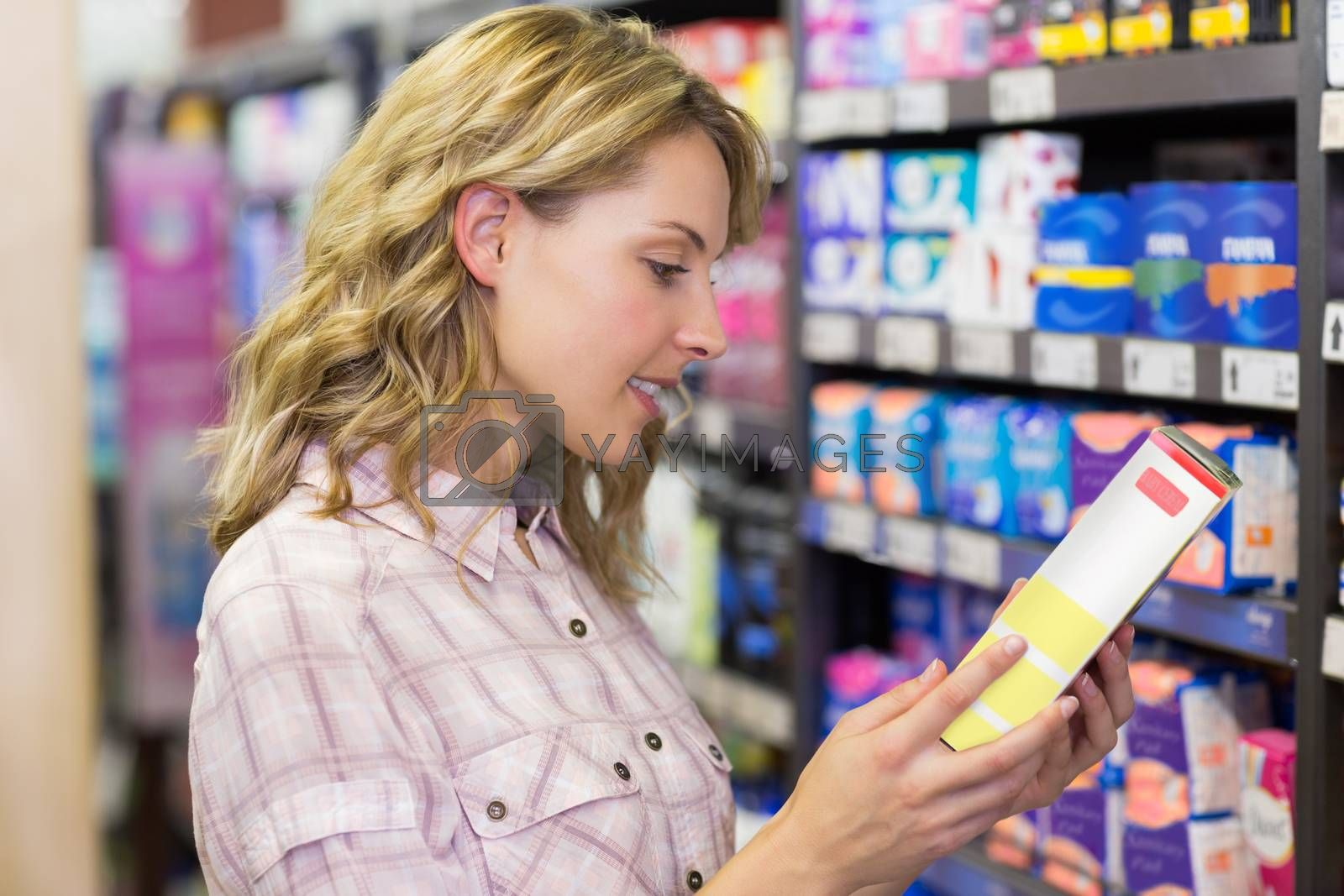 Royalty free image of Side view of smiling pretty blonde woman looking at a product by Wavebreakmedia