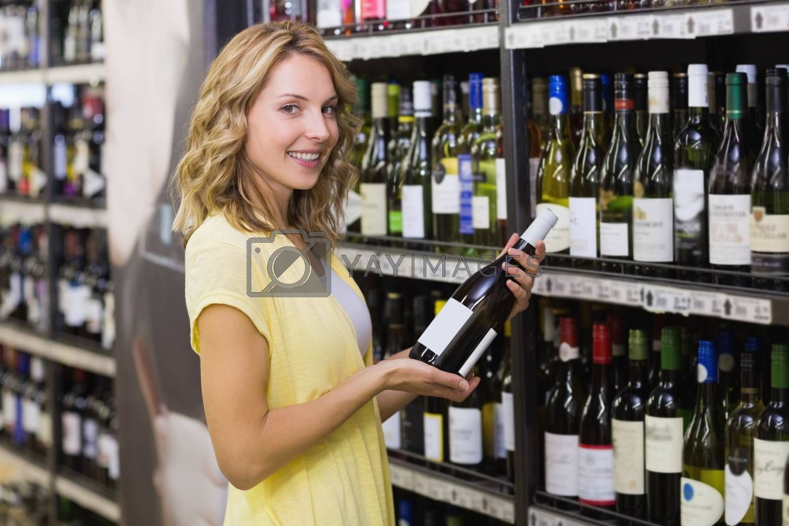 Royalty free image of Portrait of a smiling pretty blonde woman having a wine bottle in her hands  by Wavebreakmedia