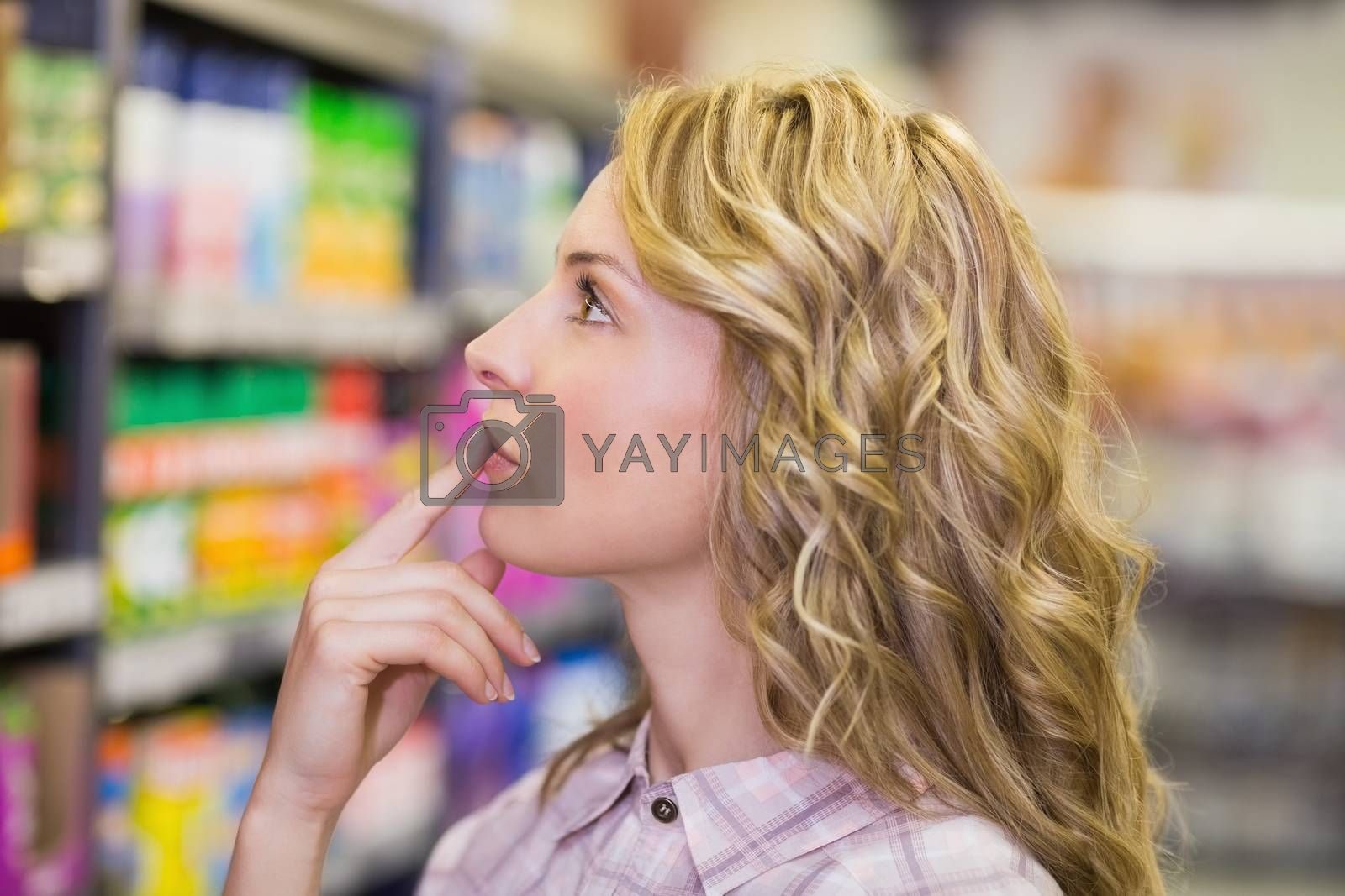 Royalty free image of Side view on pretty blonde woman looking at shelf  by Wavebreakmedia