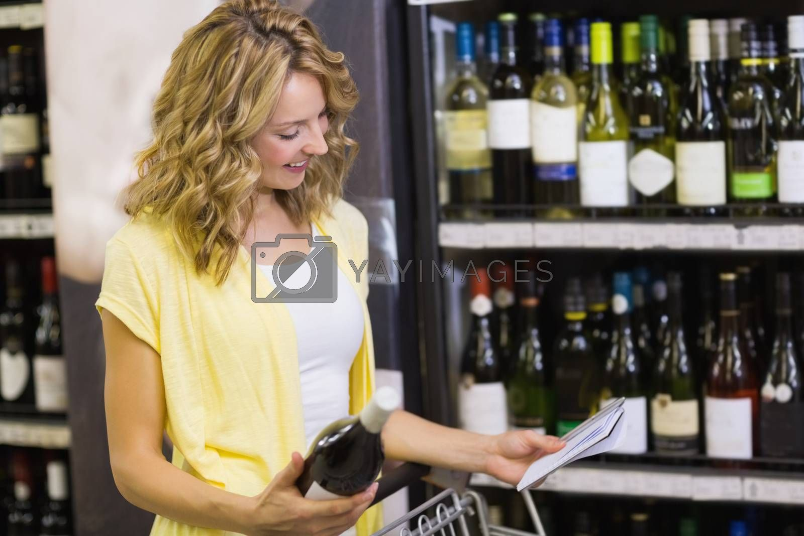 Royalty free image of Smiling pretty blonde woman looking at notepad and having in her hands a wine bottle  by Wavebreakmedia