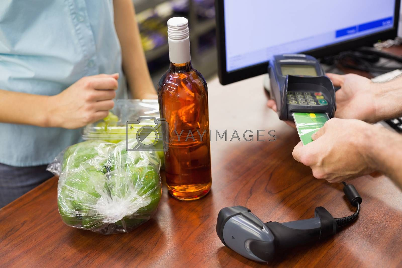 Royalty free image of Woman at cash register paying with credit card by Wavebreakmedia