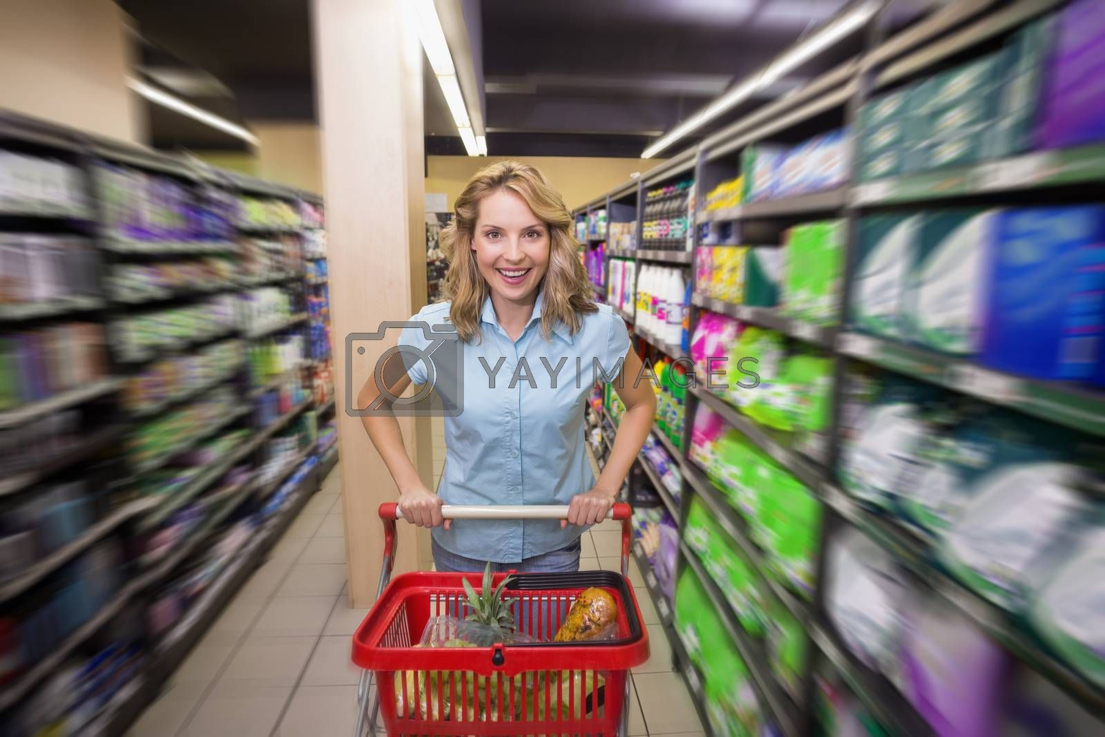 Royalty free image of Portrait of a smiling woman is aisle with her trolley  by Wavebreakmedia