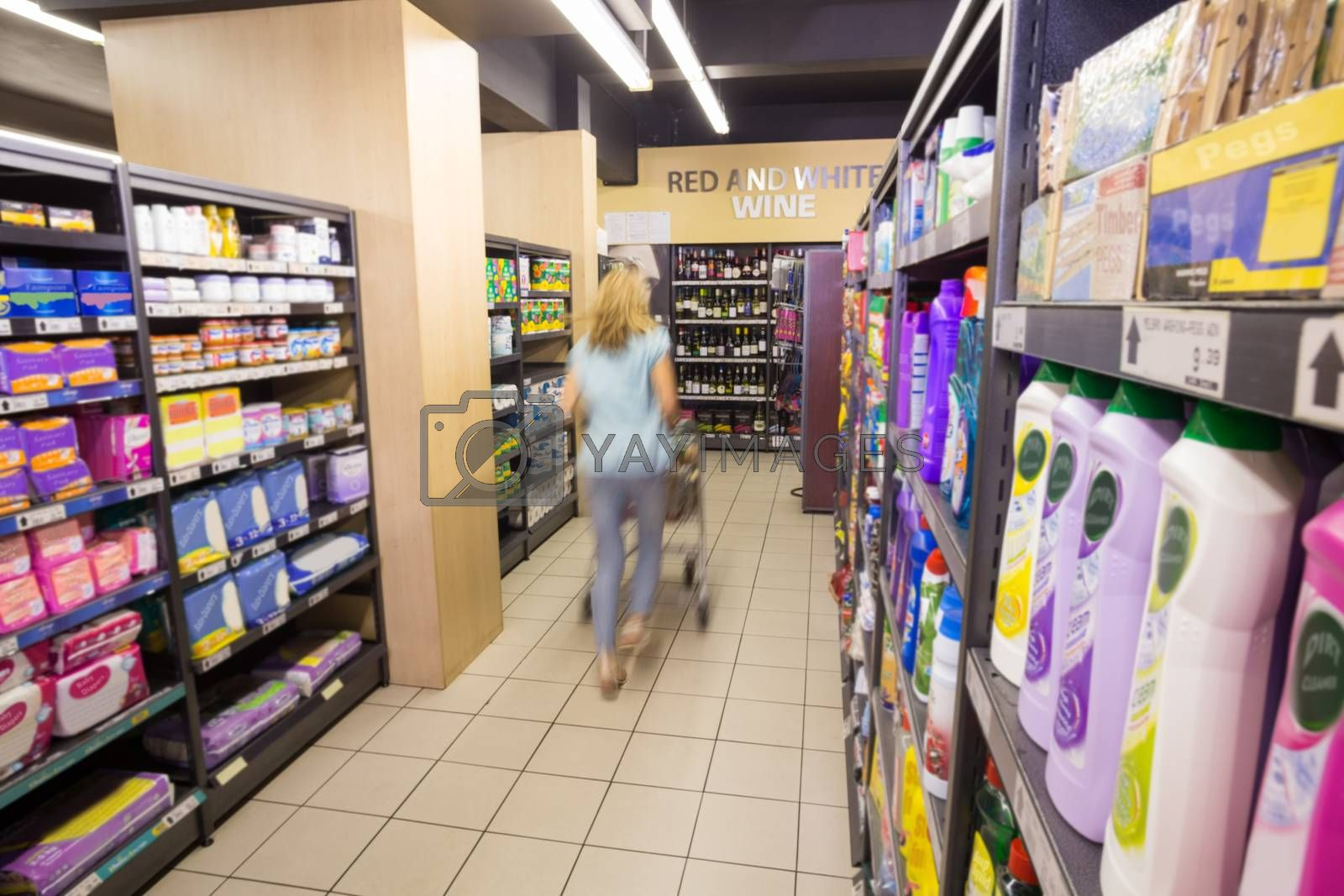 Royalty free image of A woman walking in aisle with her trolley  by Wavebreakmedia