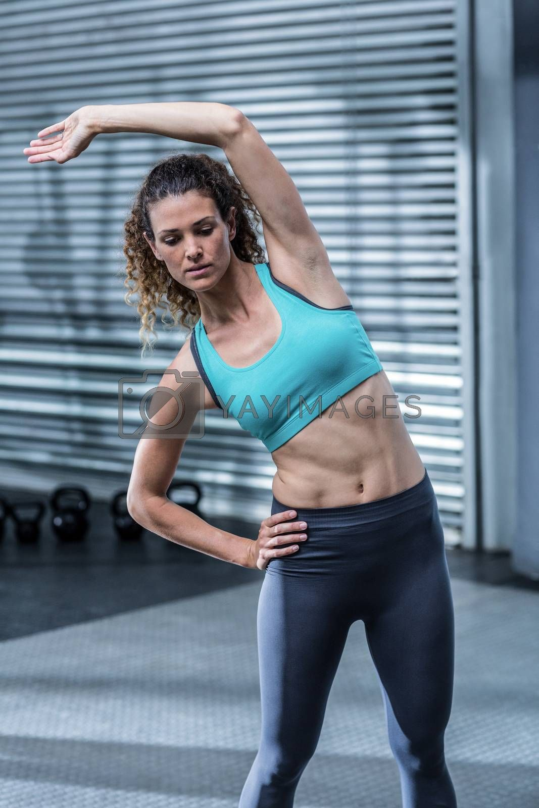 Muscular woman stretching her body at the crossfit gym