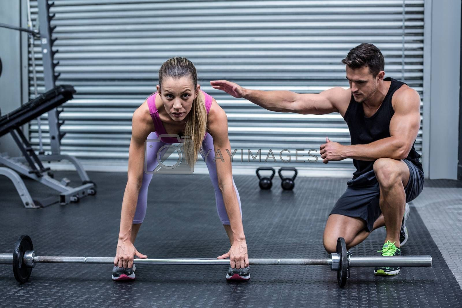 Attentive muscular woman lifting weight with her trainer besides