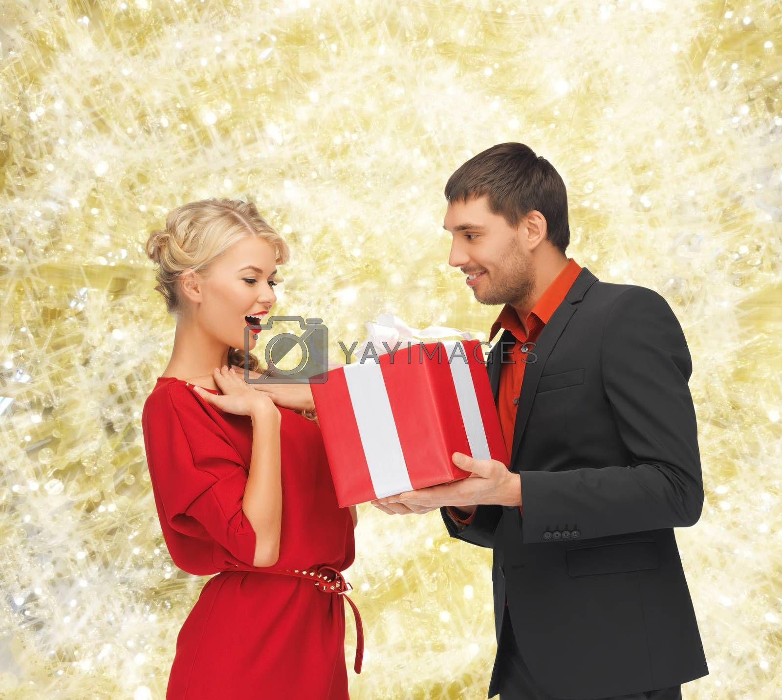christmas, holidays, valentine's day, celebration and people concept - smiling man and woman with present over yellow lights background