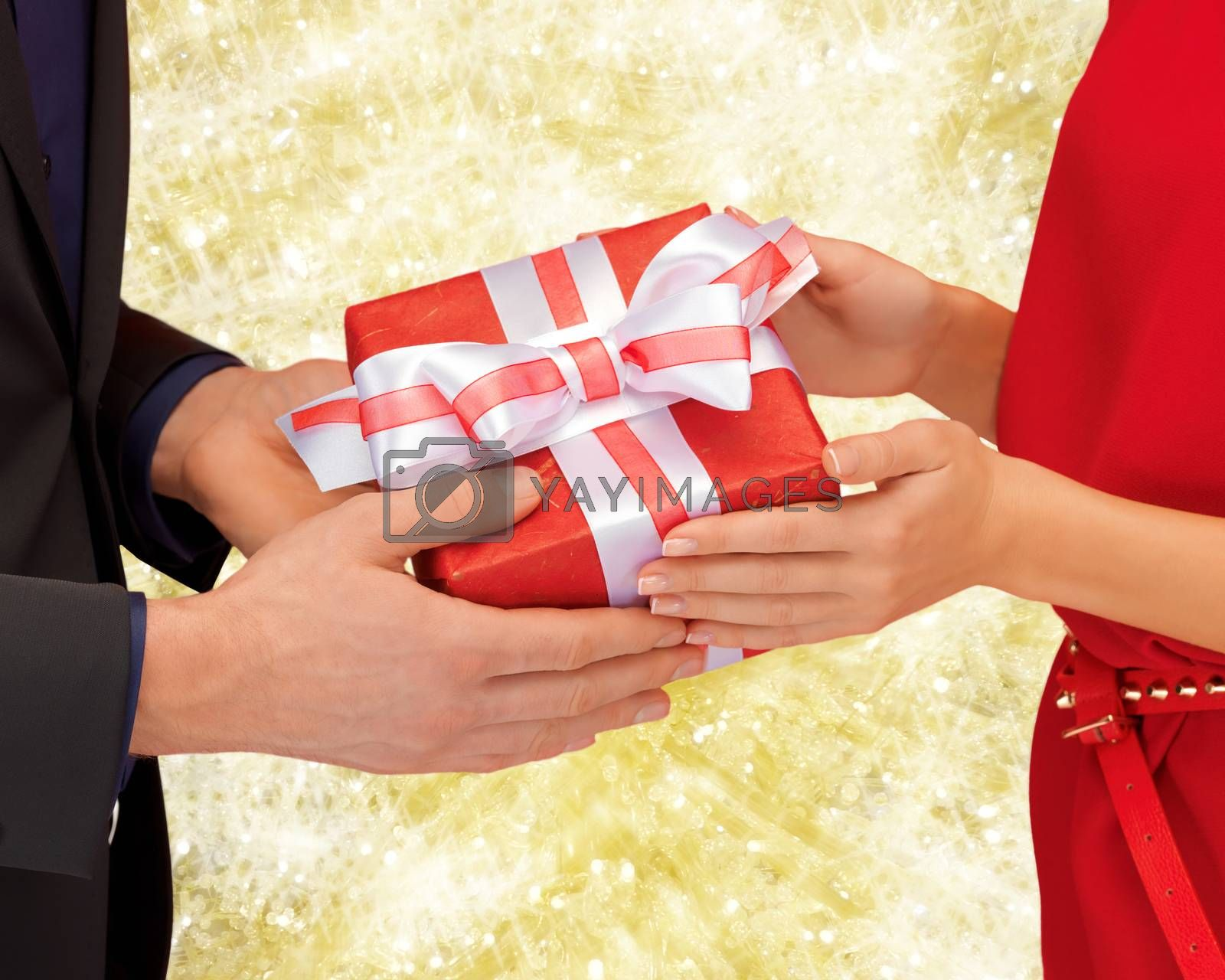 christmas, holidays, valentine's day, celebration and people concept - close up of man and woman with present over yellow lights background