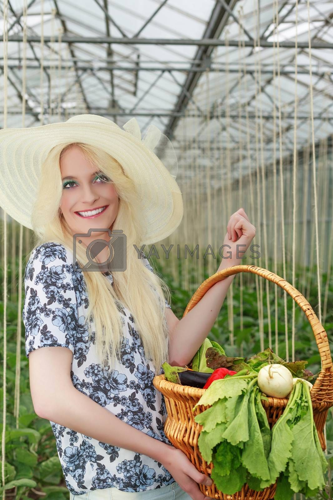 Pretty Blond Woman Wearing Straw Hat, Carrying Basket of Fresh Veggies on her Arm Inside the Farm and Looking Into the Distance.