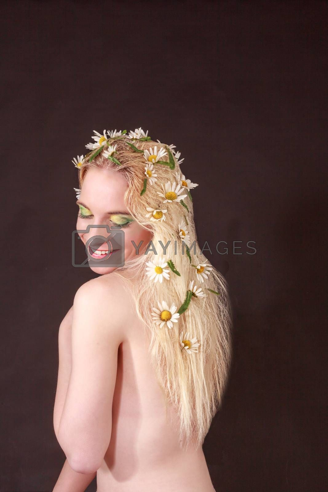 Half Body Shot of a Happy Bare Young Woman with Flowers on her Long Blond Hair, Looking on her Shoulder Against Black Background.