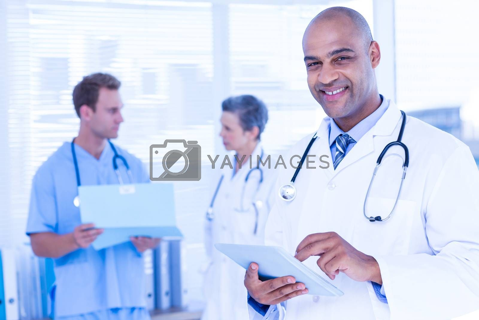 Royalty free image of Smiling doctor using his tablet by Wavebreakmedia