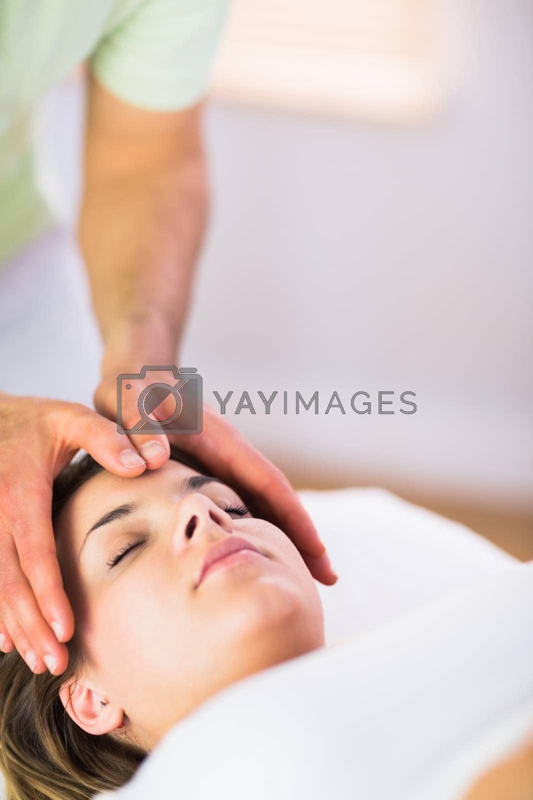 Royalty free image of Relaxed pregnant woman getting reiki treatment by Wavebreakmedia