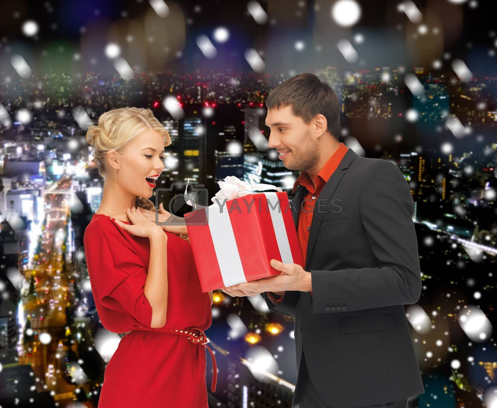 christmas, holidays, celebration and people concept - smiling man and woman with present over snowy night city background