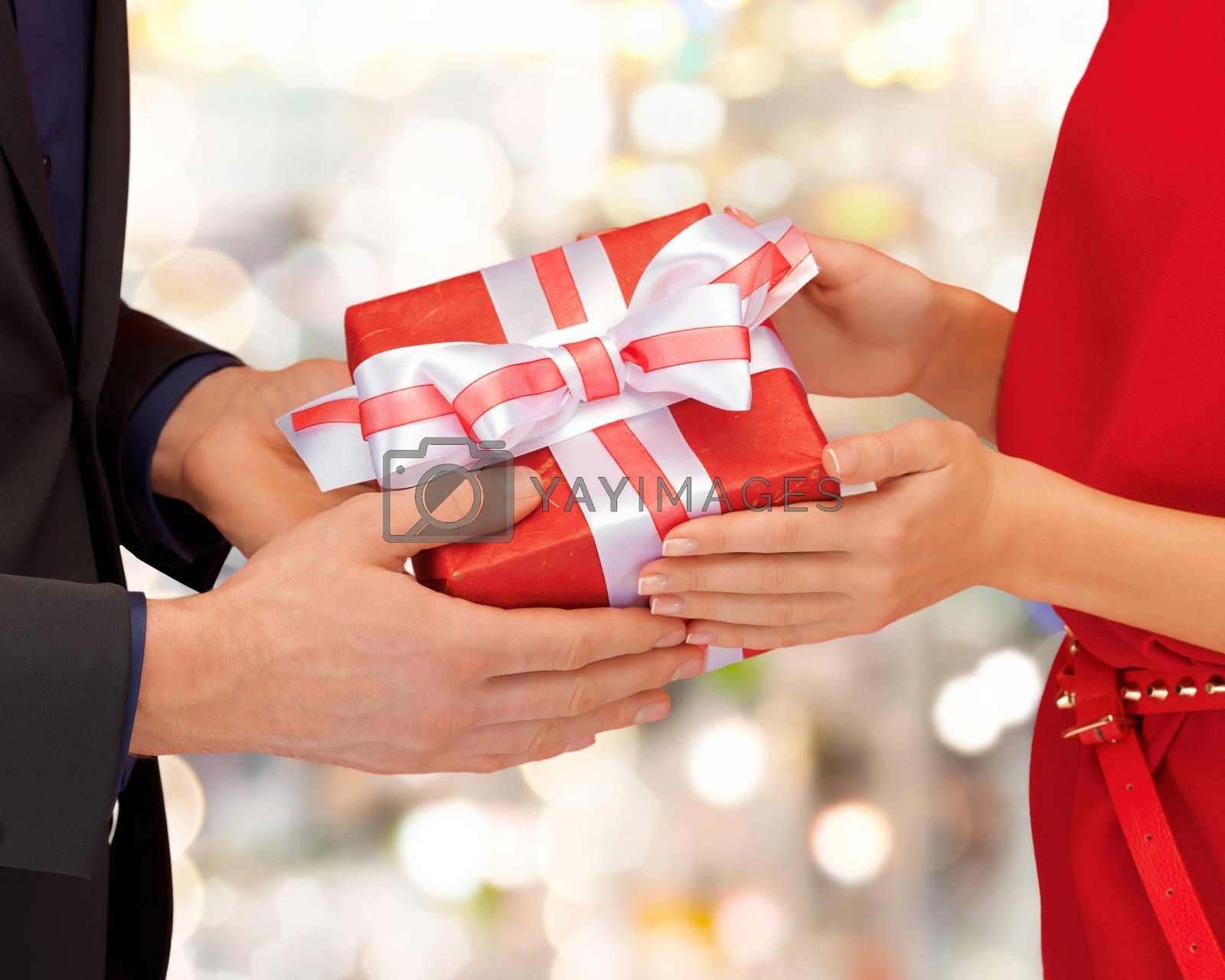 christmas, holidays, valentine's day, celebration and people concept - close up of man and woman with present over lights background