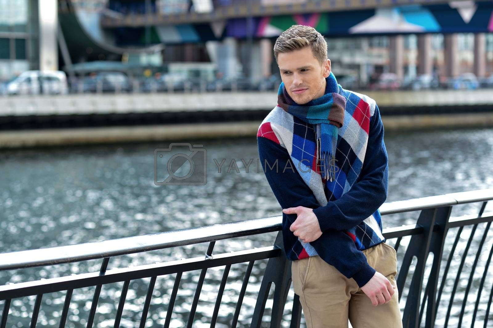Young man leaning on metal railing at outdoors