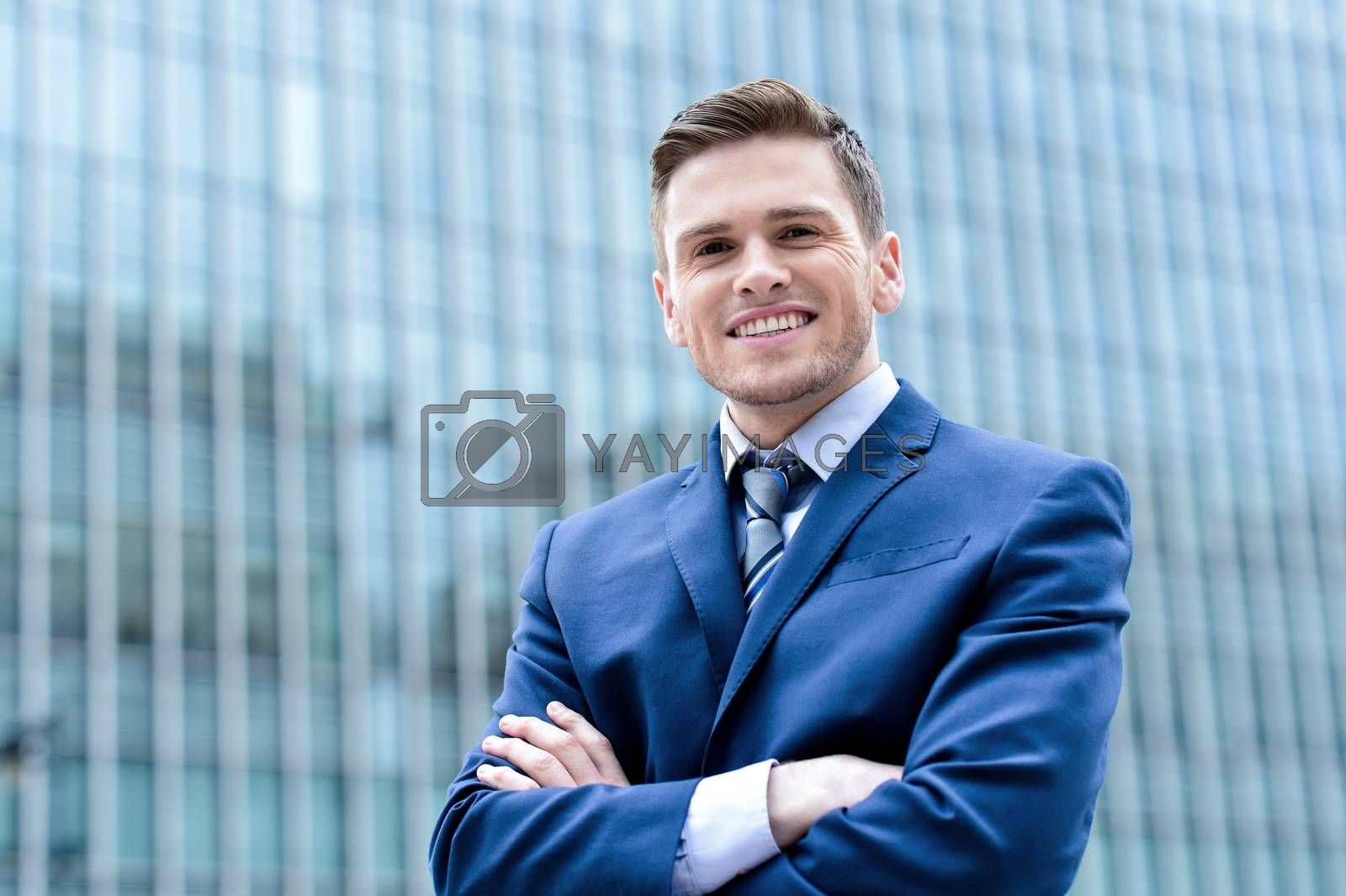 Confident businessman posing with folded arms outside skyscraper