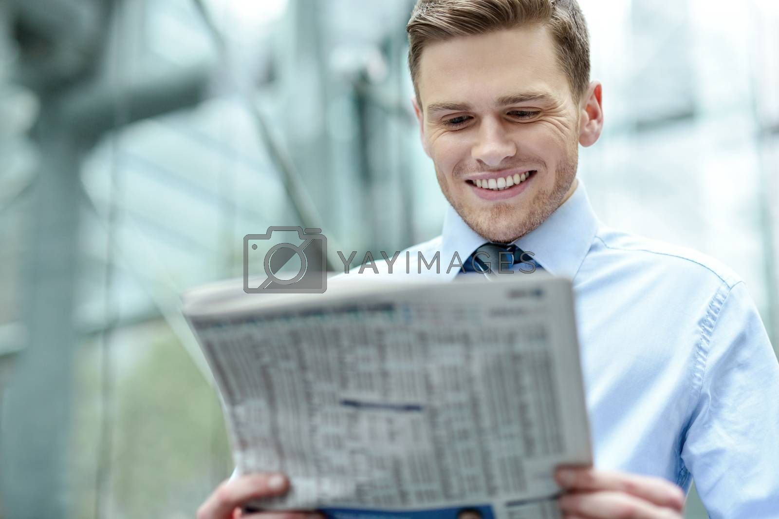 Image of a happy corporate male reading newspaper