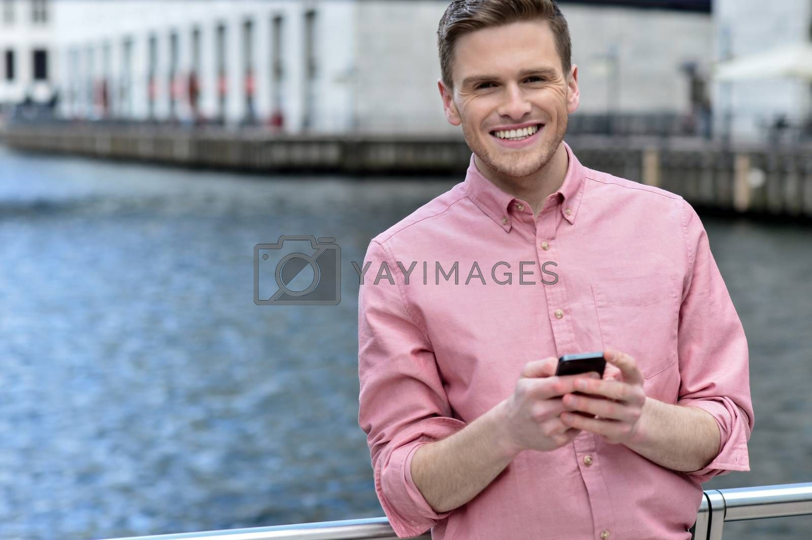 Happy young man posing with his mobile phone