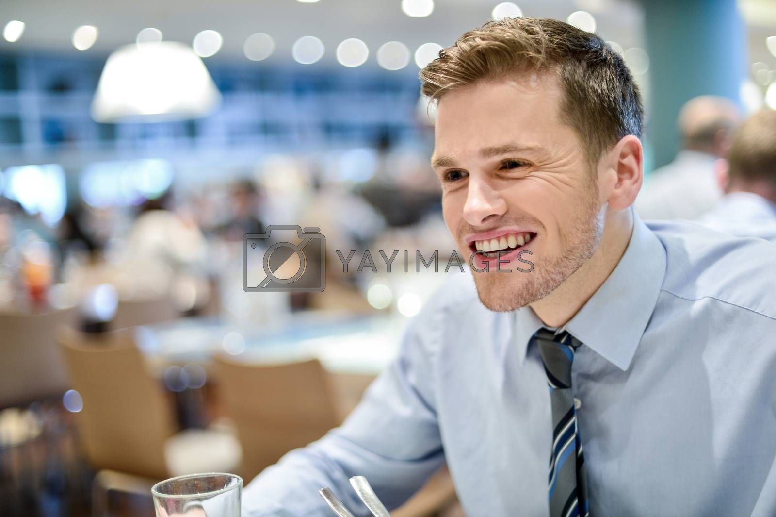 Relaxed smiling corporate male sitting in restaurant