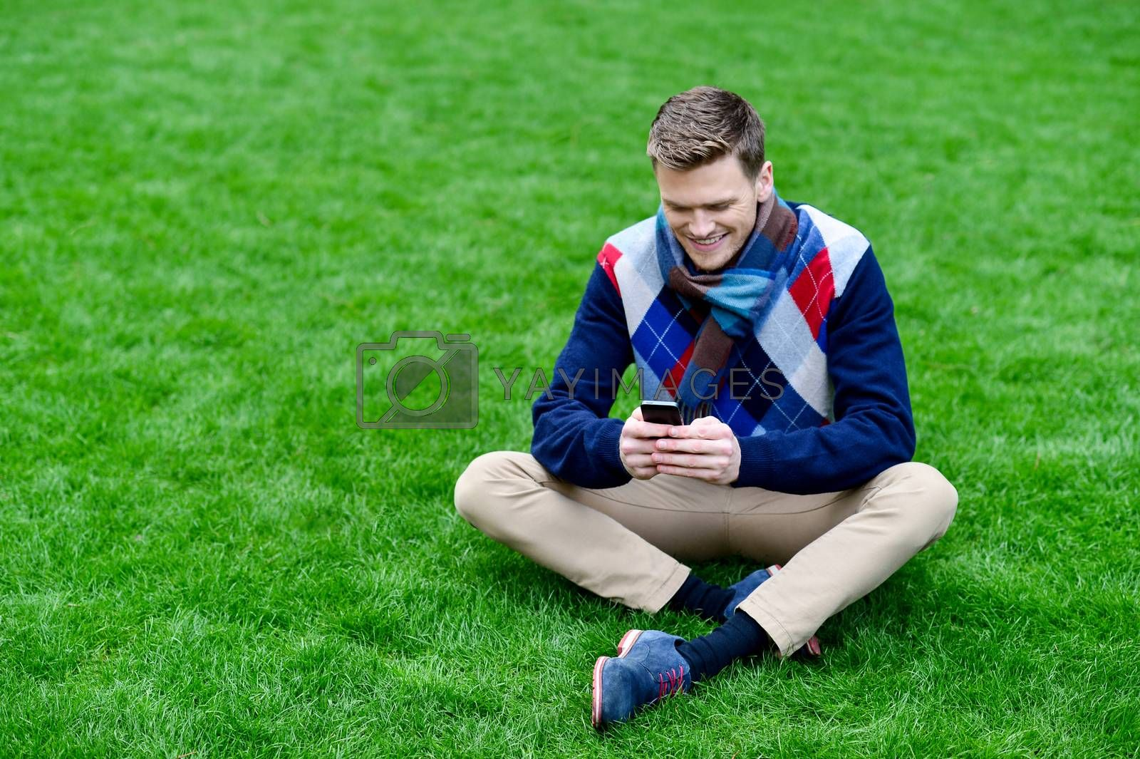 Young man playing with his mobile at park