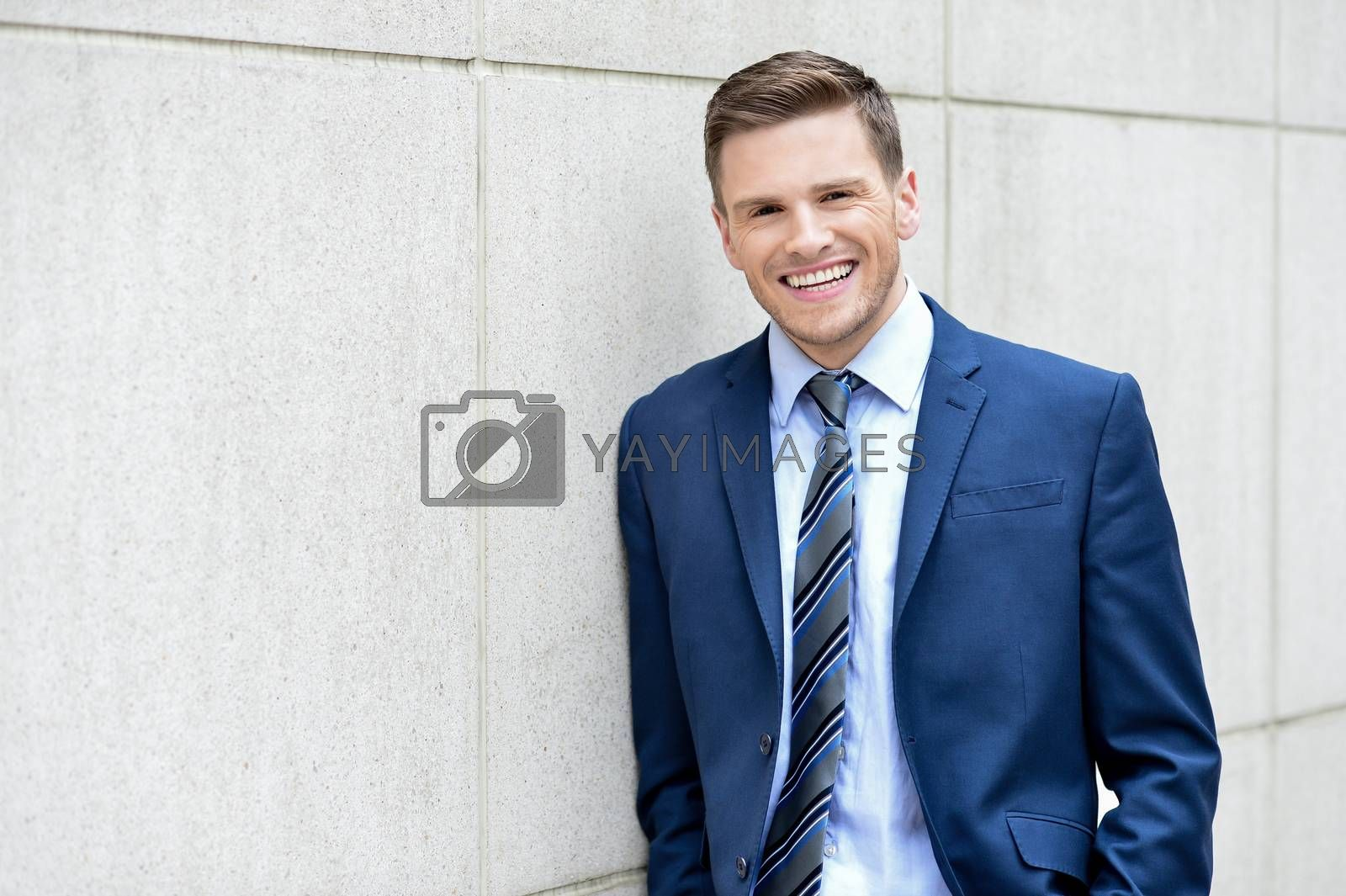 Image of a happy businessman leaning against a wall