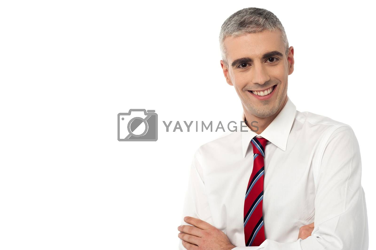 Handsome male executive with crossed arms over white