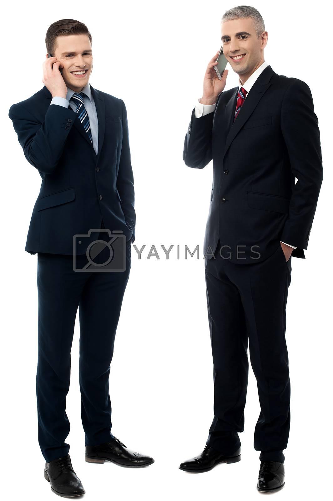 Portrait of handsome businessmen communicating via cellphone