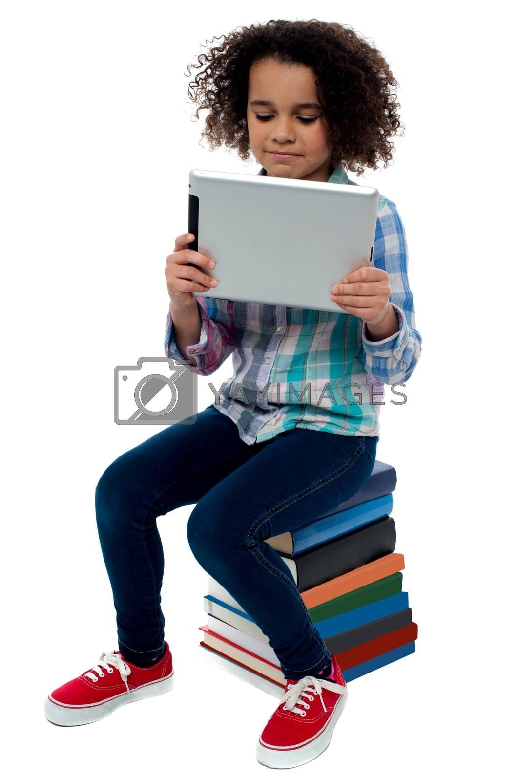 Little girl sitting on books with digital tablet