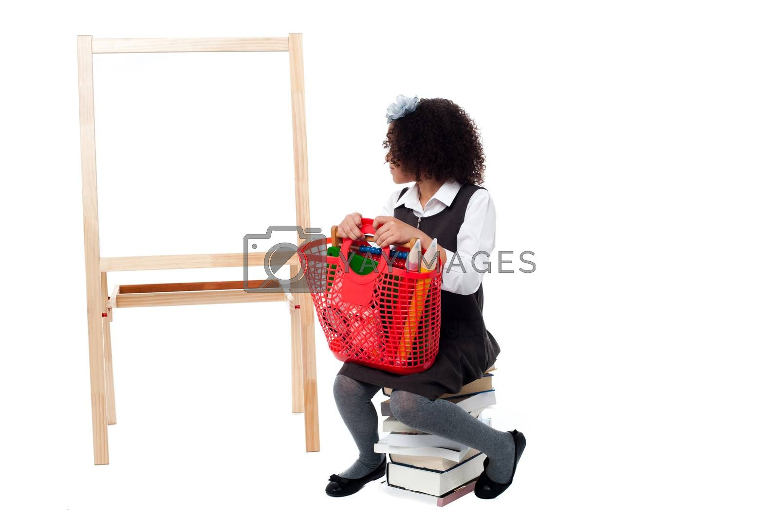 School girl sitting on books, watching the board