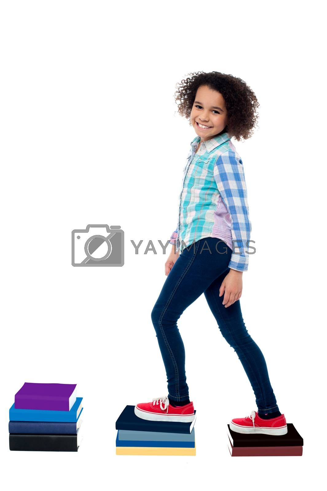 Pretty girl child climbing on notebooks over white